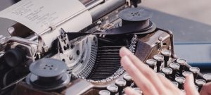 Person writing self-published work on a typewriter