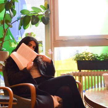woman sitting in armchair with book